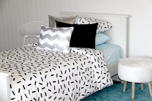 Jemima black sprinkle quilt cover, pastel blue sheeting, silver chevron cushion, aquamarine rug